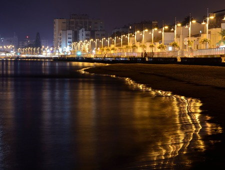 Golden evening on Larnaca seafront with lanterns and reflection on the beach.It is a city on southern coast and capital of eponymous district.