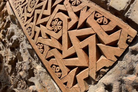 Traditional geometrical muslim ornaments with fertility swastika symbol on the medieval Karakhanid s tomb in Uzgen,Osh Region, Kyrgyzstan