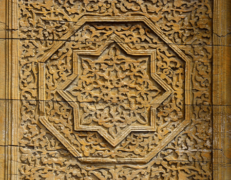 Beautiful wooden octagonal star rosette with floral pattern -  details of medieval Karakhanid s tomb door in Uzgen,Osh Region, Kyrgyzstan,