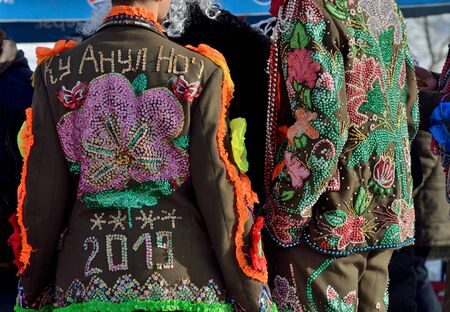 Young ukrainian men dressed in carnival military uniform decorated with beads and spangles perform Malanka song during ethnic festival of Christmas carols in open-air museum of folk architecture