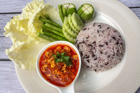 Nam phrik ong is a popular Thai food in Northern Thailand. Composition with rice, pork and fresh vegetables as cucumber, Chinese cabbage, cow pea, eggplant.