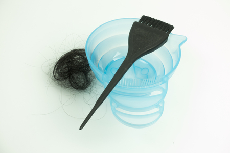 Back brush put in color bowl for hair dye and pile of hair loss on white background.