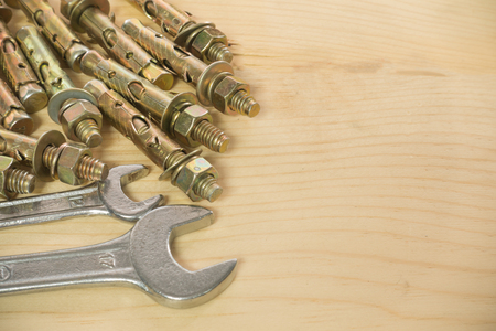 box size: wrench Bolts and screws used in construction on the wood background.