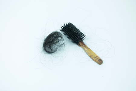 hairpiece: pile of hair loss and comb on white background.