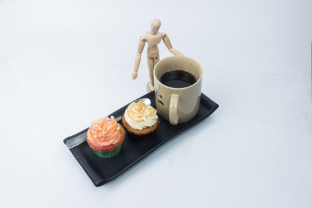 butter icing: Tasty cupcake with butter cream icing and coffee on white background
