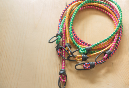 color elastic rope with hook on wood Stock Photo