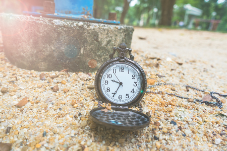 12 o clock: Vintage pocket watch on the sand on the playground. Stock Photo