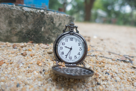 Vintage pocket watch on the sand on the playground. Stock Photo