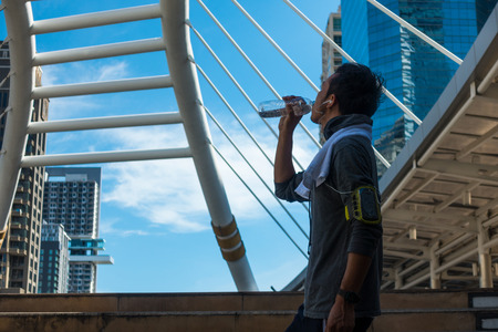 man drinking water: Asian young man drinking water after exercise within the city. Stock Photo