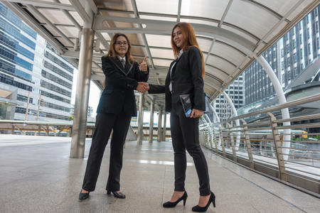 Two asian businesswomen shake hands with in city. Stock Photo