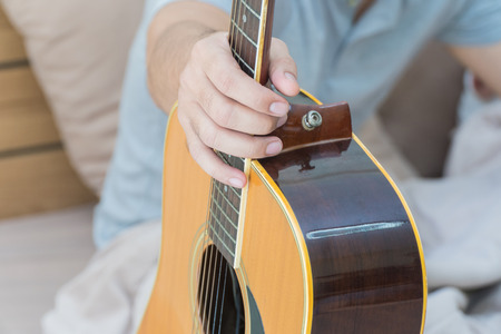 plucking: Young man holding a guitar on the bed in the bedroom.Focus hand Stock Photo
