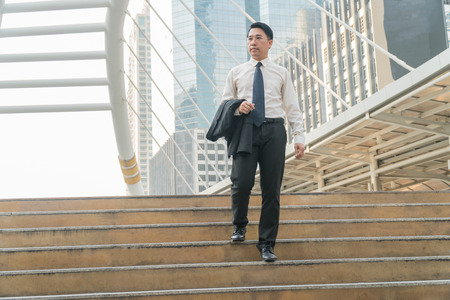 Asian middle-aged businessman walk down the stairs in modern city.
