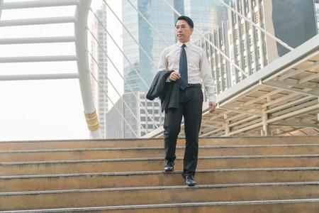 bajando escaleras: Empresario de mediana edad asiático caminar por las escaleras en la ciudad moderna.