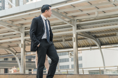 bajando escaleras: Asian middle-aged businessman pick up hand walk down the stairs in modern city.