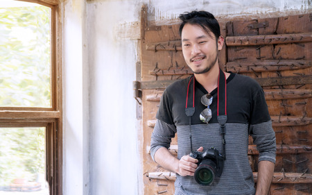 Handsome young male photographer holding digital camera and smiling to camera while standing on wooden door. Lifestyle concept.