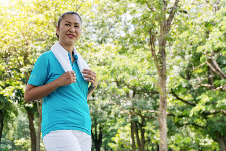 Elderly lifestyle concept. Attractive senior woman 50s feeling happy and wellbeing with white towel on neck exercises in the public park. Stock Photo - 110304628
