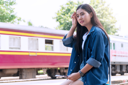 Traveler young woman feeling so hot and tired while waiting someone at train station in summer season. Attractive beautiful girl uses her hand to wipe sweating on her face.