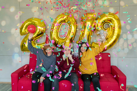 Group of cheerful asian young people friends sitting on red sofa carrying balloon gold colored numbers and throwing confetti on the party. New 2019 Year is coming Celebrate. Bokeh light soft effect.