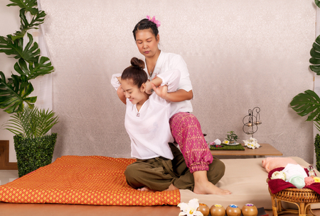 Concept thai Massage. Beautiful Asian young woman getting herbal massage thai massage in spa salon.Thai girl reflexology on shoulder with masseur.