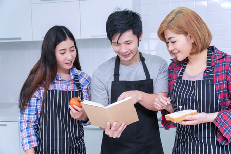 Asian Groups of friends cooking together meal food in the kitchen. Cheerful smiling young man holding book learning cook with his woman friends at home. Friendship concept.