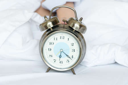 Alarm clock silver style vintage place on a bed with hands of woman holding a clock. retro analog watch on white bed in morning time. 6 o'clock with copy space.Getting enough sleep concept.