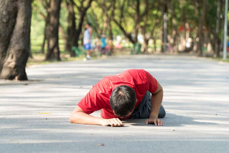 Young men wearing red shirts falling down to the pavement in public park while jogging. Concept injury from exercise.