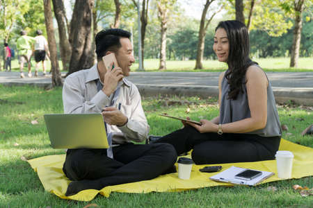 Attractive business man and woman sitting relaxed in shady park. But there is talk. Analysis of business plan. Two business people talk planned in the park.Concept success