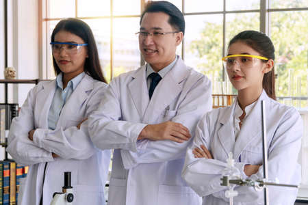 Teams of researchers in white coat and protective eyeglasses standing arms crossed together in the laboratory.