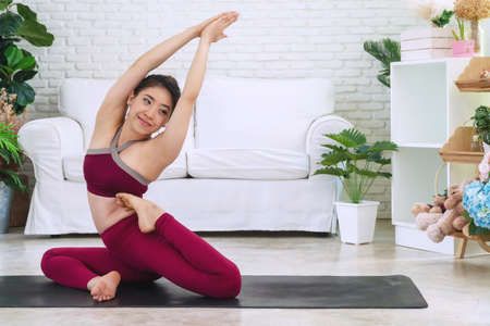 Activity young women wear red sportswear sitting on mat in front of white sofa while doing position yoga in living room. Relaxation girl practice advanced yoga at home. Lifestyle healthy concept.
