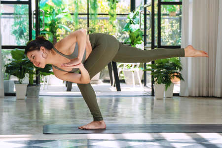 Activity young women wear green sportswear doing position detox yoga sequence on the mat. Relaxation girl practice advanced yoga keep body fit at home. Lifestyle exercise for good healthy concept.