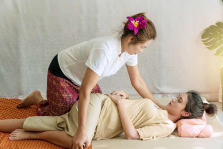 Professional masseuse woman therapy massage young girl at spa salon. Beautiful young woman lying on the pillow receiving masseuse massage for body pain at home. Healthy massage aromatherapy concept.