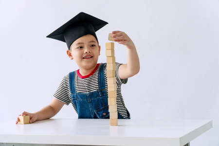 Little cute boy concentrate wooden block on table while sitting in the white room. Adorable pigtails childhood attention playing wooden toy. Primary education concept.