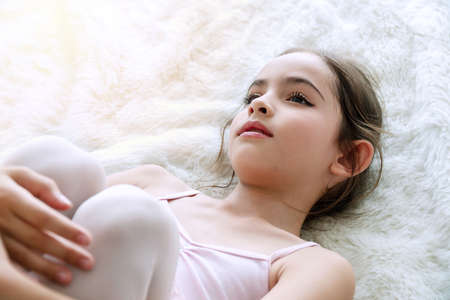 Adorable cute little ballet girl brown long hair lying on white fur rug while looking at camera . Top view lovely kid lying down relax on her dress. Kid ballet and performance art for modern concept. Banco de Imagens