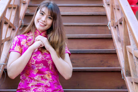 Enjoy young woman wearing pink cheongsam or qipao sitting on stair while raising her hand to bless her to be happy and healthy. she looking at camera with smile. Chinese new year concept.