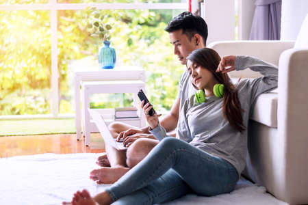Young man using laptop working online while sitting on floor in front sofa together with his girlfriend looking at smartphone in hands. Young woman with headphones shopping online with phone at home.
