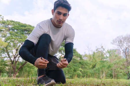 Athletic young man kneeling while tying sports shoes in the park looking at camera. Handsome male shoelace on green grass with big tree in the park. Healthy workout concept.