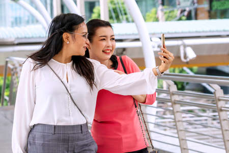 Two middle-age woman talking selfie photo with smartphone while walking together in street at urban city. Cheerful traveler female with friends looking at mobile phone in their hands.