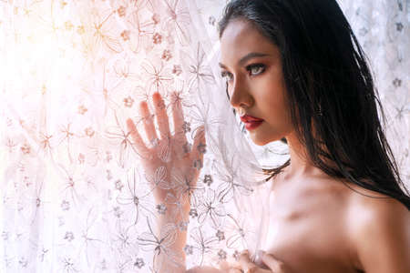 Face of Slim young woman looking at something while standing beside window. Perfect body lady black long hair touches curtain fabric while standing front of windows with sunlight lonely at home. Banque d'images