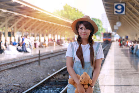 Traveler young woman with brown teddy bear standing at railroad station platform while waiting track in vacations. Portrait lady wear hat standing in train station while holding teddy bear in hands.