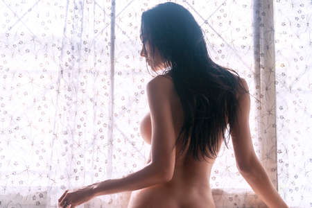 Black of Slim young woman looking at something while standing beside window. Perfect body lady black long hair touches windows while standing front of windows with sunlight lonely at home.