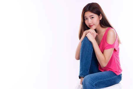 Joyful young woman with long hair wear pink t-shirt showing palm hand while sitting on chair over isolated against white background.