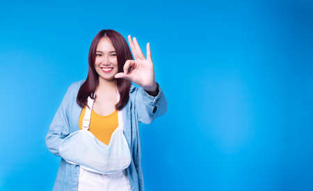 Patient young woman wearing soft splint armband while make hand sign ok standing on blue isolated on blue background. Insurance accident concept.