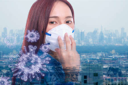 Double exposure of young woman wear protection N95 mask to protect with 3D virus, PM 2.5 dust or air pollution over smoke city building background. Social distancing and health care concept.