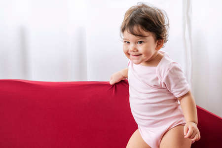 Little cute baby girl play on red sofa at home. Enjoy one year old child mixed race smiling while standing on the couch. Adorable toddler wear pink bodysuits dancing on sofa cushion in living room.