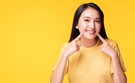 Cheerful young woman using finger point to her whitening teeth while standing over isolated yellow background. She showing her cleaning fresh toothy. Dental care and healthy concept.