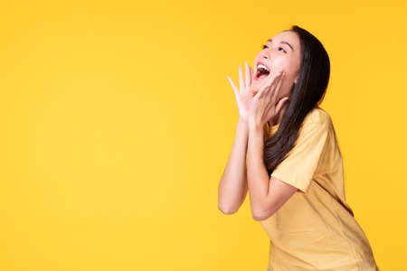 Young woman covers her mouth surprised excited while looking at product on sale promotion or empty copy space over isolated yellow background.