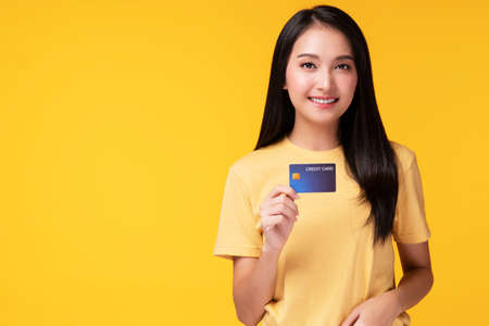 Payment purchase and financial concept. Cheerful young woman wearing casual clothes while holding hand and credit card mockup while looking at empty copy space over isolated white background. Foto de archivo