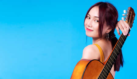 Happiness young woman with an acoustic guitar behind her back on blue background. Portrait cheerful female holding guitar on her back while standing on isolated background.