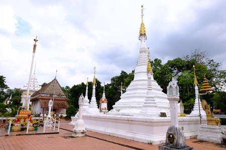 The white Myanmar Pagoda style in front of ancient Thai style ordination hall at Nonthaburi, Thailand December 2018. In beside, the main ancient ordination hall with Glazed porcelain decorated with stucco, floral vines, stucco art. 免版税图像