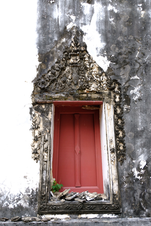 The Thai art stucco of Window frame isolated with white color and red wood color frame. The window frame isolated with the art of craftsmanship is beautifully external decorated in ancient authentic Thai style. 免版税图像